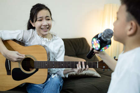 Happy asian child girl,kid boy singing a song together at home,family concert,sister plays the guitar,little brother hold a microphone sing,having fun,enjoying,stay home quarantine,children lifestyle