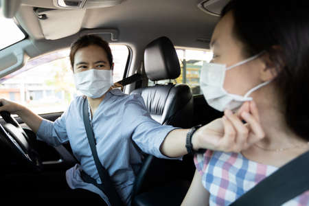 Asian woman,child girl in protective face masks with fastening seat belt in car,mother help care her daughter wear medical mask before traveling on a trip together,preparation prevention of new normal Zdjęcie Seryjne