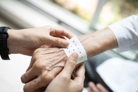Hands of senior with analgesic sheet, plaster to stick on the wrist of the old elderly to relieve muscular pain,plaster cover the patient's pain area on skin to release sprain,body ache relief Zdjęcie Seryjne