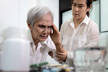 Asian elderly suffering from headache,painful cranial neuropathies,facial pains,stressed senior woman with tension type headache,high blood pressure,health problems of old people,health care concept