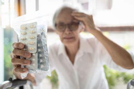 Old elderly holding medicine pills in her hands,female patient touch her head suffer from headache,high blood pressure,painful,stressed senior woman with tension type headache,migraine,health problems