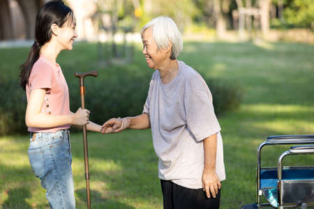 Happy asian child girl holding hand,taking care,support for old elderly,granddaughter invited the senior woman to practice walking with walking stick while visiting grandmother, health care concept