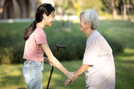 Asian granddaughter is giving a walking stick to her old grandmother,persuade her senior woman to take a walk,exercise in the garden together,happy child girl visiting the elderly at nursing home Zdjęcie Seryjne