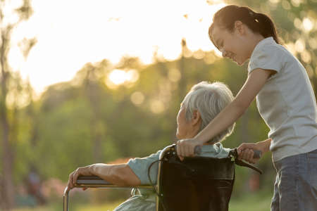 Happy senior disabled woman in wheelchair with granddaughter walking outside at park on sunny day,smiling child girl and elderly grandmother,love,family spending time together outdoor in sunset nature