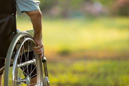 Main d'une personne âgée handicapée à l'extérieur dans la nature verdoyante du parc, espace de copie, vieille femme assise sur son fauteuil roulant avec impatience, femme âgée asiatique déplaçant son fauteuil roulant seule à l'extérieur le matin