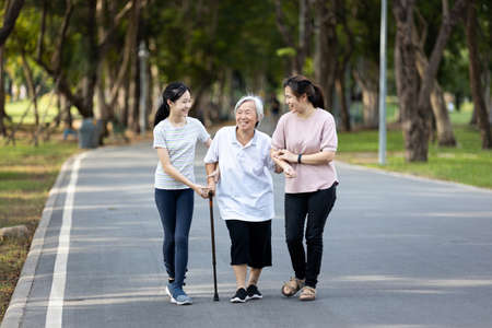 Happy asian family strolling embracing while relaxing and enjoying summer day in city park at leisure,smiling senior grandmother,mother,daughter child walking holding hand together along the promenade Zdjęcie Seryjne