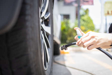 Hands of female driver is spraying alcohol into a compressor before touching,filling air in the tires,disinfection using spray alcohol during the Coronavirus,COVID-19 pandemic,new normal life concept