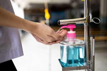 Hands of asian girl washing hand with hand sanitizer,tool, equipment  of alcohol antiseptic gel,use feet instead of hands,reduce touch,disinfection of Coronavirus,COVID-19,health care,new normal life