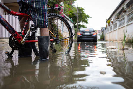 Person wear rubber boots,prevent infection of leptospirosis,athlete's foot,disease from dirty water,male in waterproof boots in a puddle on a flooded street,car is driving through floods in background