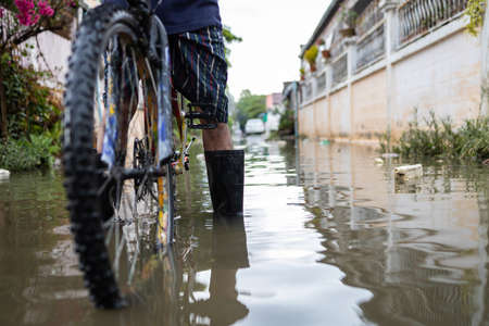 Legs with rubber boots in flooding,Asian man wear waterproof boots with his old bicycle in flooding,after heavy rainfall on the street,person riding a bicycle on a flood,storm during the rainy season Zdjęcie Seryjne