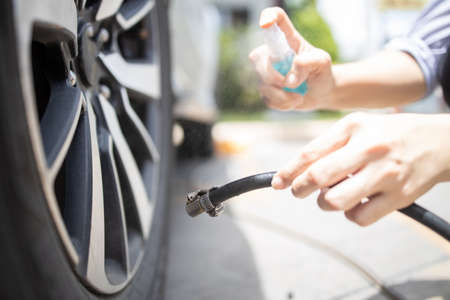 Hands of woman is spraying alcohol disinfectant into a compressor before filling air in the tires,check air pressure,cleaning with hand sanitizer spray before touching public objects,new normal life Zdjęcie Seryjne