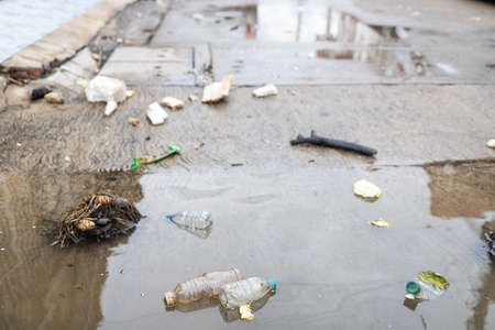 Lots of garbage,littering,many old plastic bottles float on the water surface after heavy rain and flooding,waste and dirt rubbish causes flooding on the street,pollution,environmental conservation