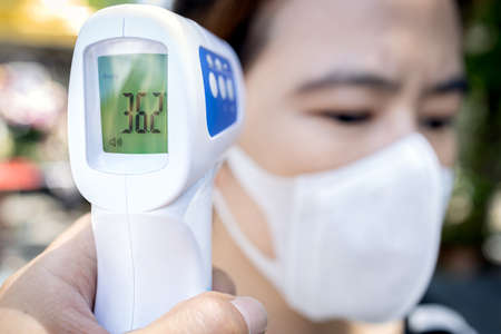 Measures to prevent people with fever,Coronavirus,against the spread of COVID-19,wear face mask and screening point using infrared thermometer,check body temperature without contact,New normal life