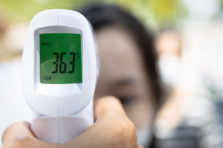 Close up of infrared digital forehead thermometer in hand,fever examination,measures to prevent,screen people check body temperature during its reopening after COVID-19 Coronavirus Lockdown,New normal
