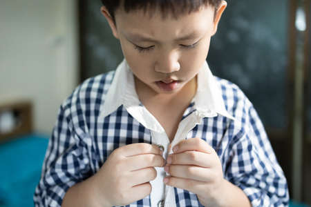 Hand of little child is trying to wear shirt,asian student buttoning his shirt at home,kid boy kindergarten self learning to change clothes dressing before back to school,lifestyle,skills,development Zdjęcie Seryjne