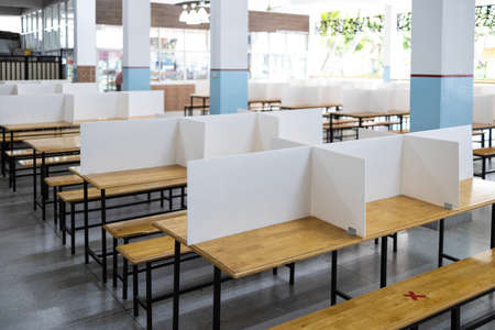 Corrugated plastic sheet partition on the tables in the cafeteria at school during its reopening,plastic shield as a barrier to prevention of infection,safety of students,social distancing,new normal