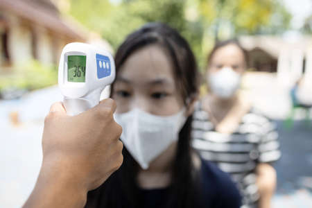 Asian student girl wear medical face mask is checking fever outside of school during its reopening after COVID-19 lockdown,screen people check body temperature with contactless thermometer,new normal