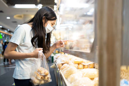 Asian child girl wear face mask,buying bread in bakery have a plastic shield partition between customers at shopping mall during its reopening,prevent of infection,social distancing,safety,new normal