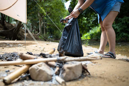 Asian people collecting litter with garbage bag at the national park,tourist pick up trash waste after camping in nature forest,tent and stream in background,caring for environment,ecology protection Zdjęcie Seryjne