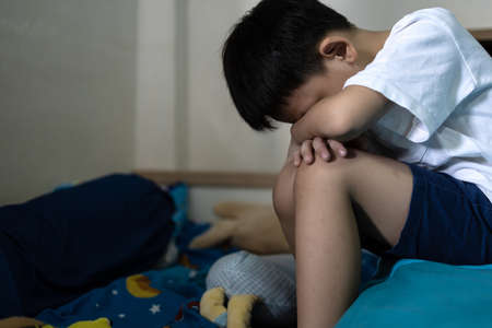 Regret sad asian little boy sitting alone loneliness,stressed depressed child crying having depression,anxiety,trouble of mental health,lonely kid boy with hands on knees,Hikikomori Syndrome Disease