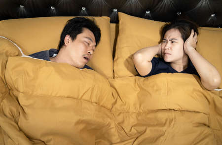 Asian man snoring with open mouth,wife is closing ears with hands,stressed by loud noise,annoying snoring of husband,risk of sleep apnea while sleeping,unhappy woman wakes up while lying in the bed