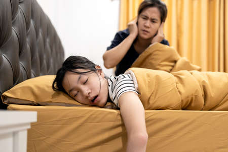 Asian daughter snoring loudly,open mouth,drooling on pillow,comfortably sleeping,annoying snoring of child girl,danger of sleep apnea disease,stressed woman or mother wakes up,closing ears with hands