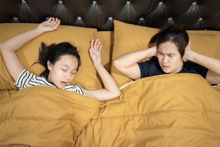 Asian teen daughter snoring with open mouth,mother is closing ears with hands,loud noise,annoying snoring of child girl,risk of sleep apnea while sleeping,unhappy woman wakes up while lying in the bed Stok Fotoğraf