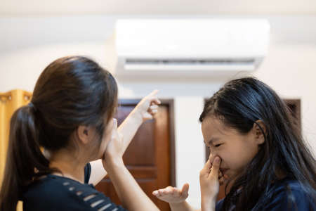 Asian woman and child girl are closing her nose, bad smell,musty smell of air conditioner has a problems,dust and dirt coming in through the air ventilation,concept for cleaning check air conditioner 版權商用圖片