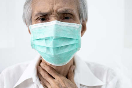 Sick senior in protective mask,old people has sore throat,cough,fever and phlegm in the throat,illness symptom of COVID-19 infection,elderly woman wear face mask to prevent the spread of Coronavirus