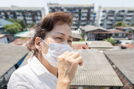 Sick asian senior woman wearing protective mask when having flu,fever,coughing to reduce the risk the spread of Coronavirus disease to others,prevent spreading of COVID-19,new normal,stronger together