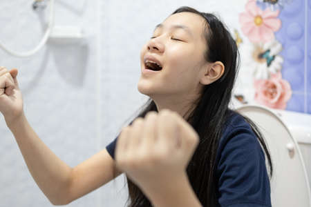 Defecation and urination,Happy asian people sitting on the toilet,emotions and gestures facial expressions happy,defecating in the bathroom,child girl with relief and satisfaction after constipation