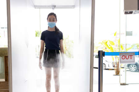 Asian child girl wear face mask,automatic disinfection tunnel is spraying on body for disinfecting at gate check point for COVID-19,measures to prevent,process of cleaning,new normal under Coronavirus
