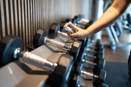 Hand of asian woman spraying alcohol into a dumbbell to clean it,people cleaning of sport equipments with disinfecting spray in the gym or fitness