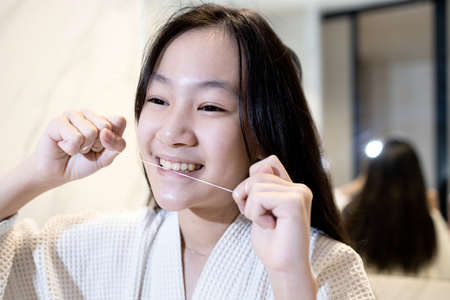Happy smiling asian girl flossing her teeth,clean her healthy teeth before going to bed at night,beautiful child girl brushing with dental floss in the bathroom, teeth care,oral hygiene,dental health 版權商用圖片