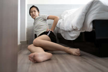 Asian child girl was sitting in pain on the floor after she fell out of bed while sleeping,injured,sad woman holding hip with her hand,suffering from pain after sleepwalk,problem of parasomnia disease