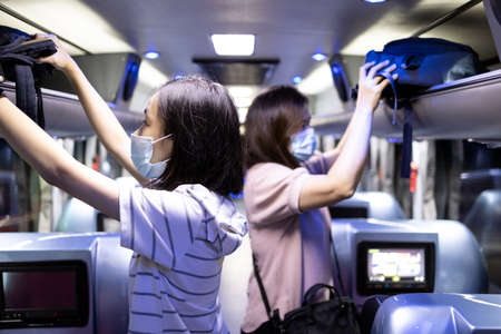 Asian passenger stowed her backpacks in a overhead storage on the tour bus,people wearing protective masks to safety ,vacation travel trip in new normal conditions under COVID-19