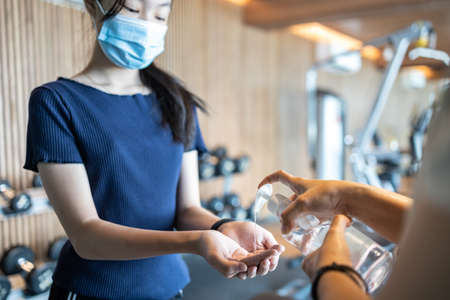 Asian teenager girl is cleaning her hands with a disinfectant alcohol gel before touching equipment in the gym,people wearing protective mask before entering the fitness,new normal under the COVID-19