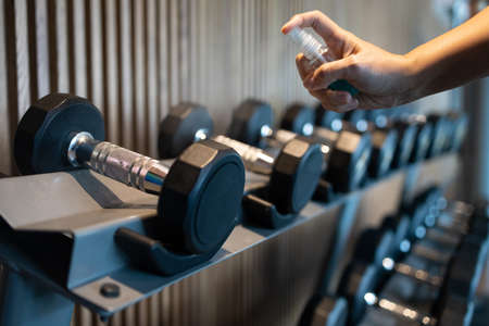 Hand of asian woman is spraying alcohol on the handle of the dumbbell to clean it,prevent infection