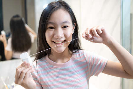 Happy smiling asian student girl flossing her teeth,clean her healthy teeth in the morning,beautiful woman brushing with dental floss in the bathroom, teeth care,oral hygiene,dental health concept
