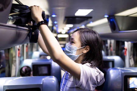 Asian female student stowed her backpack in a overhead storage on the school bus 免版税图像