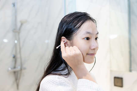 Asian child girl cleaning the external ear canal with a cotton swab,beautiful girl in white bathrobe,using cotton bud to wipe ears to dry after bathing and washing hair or removing earwax,care,hygiene