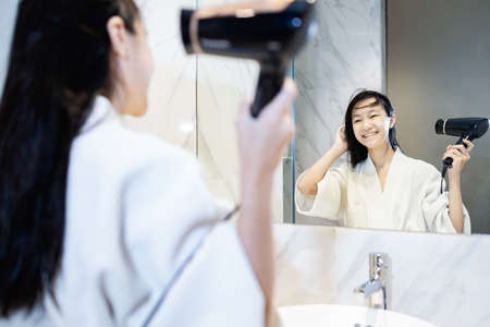 Happy asian child girl drying hair by blowing warm air with hair dryer and looking at the mirror in bathroom,beautiful smiling female in bathrobe using a hairdryer after taking a shower dries wet hair 版權商用圖片
