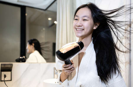 Smiling asian child girl drying hair with hairdryer,beautiful woman in bathrobe blow drying with hair dryer after hair washing,stand in front of the mirror in bathroom,daily routine, lifestyle 版權商用圖片