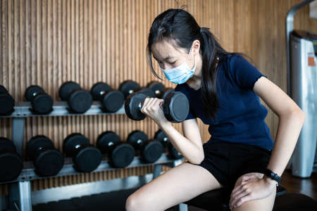 Healthy child girl exercise wearing protective face mask,protection, safety in public gyms,work out in new normal conditions under COVID-19,Coronavirus pandemic,lifting dumbbells weights for strength Standard-Bild
