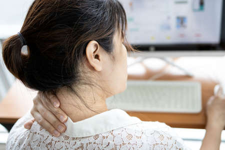 Tired asian woman with back neck and shoulders pain on muscle,stiff neck,symptom sore,painful while working,sick people have tension and injury in her scruff,office worker holding her nape of the neck