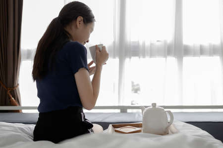 Asian girl sitting on bed drinking hot beverage in the morning,female hold the cup of herbal tea,inhales the smell and smiling with her eyes closed,good aroma of hot tea,enjoy relax her drink at home