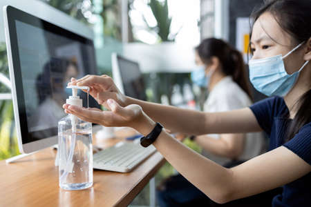 Asian student girl is pressing an alcohol antiseptic gel to disinfecting cleaning her hands before using computer,hand sanitizer for free service in school library,new normal conditions under COVID-19