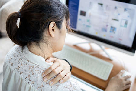 Problem of back neck,shoulders pain from incorrect sitting position,asian woman massage her muscle,bending head related to the pressure on the spine,stiff neck use a computer to work for a long time