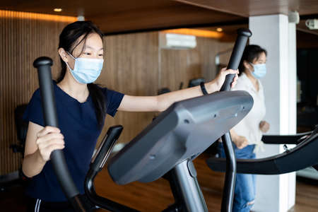 Two asian people wearing a protective masks,workout in new normal conditions under COVID-19,Coronavirus pandemic,playing exercise machines spinning bike,running on a treadmill in the gym,health care 免版税图像