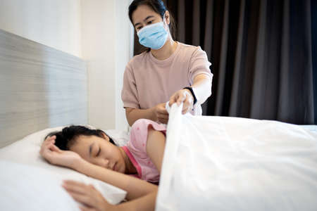 Asian woman wearing a medical mask to prevent the spread of disease,mother visits her sick daughter with a fever and cold is lying in bed at bedroom,putting up the blanket on child girl while sleep